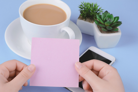 Woman's hand holding empty card with coffee and phone on a light blue background.