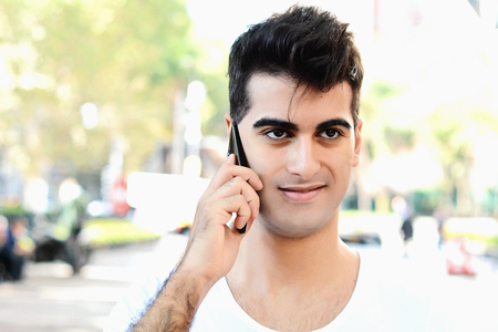 Portrait of young latin man talking on the phone in the street. Outdoors.