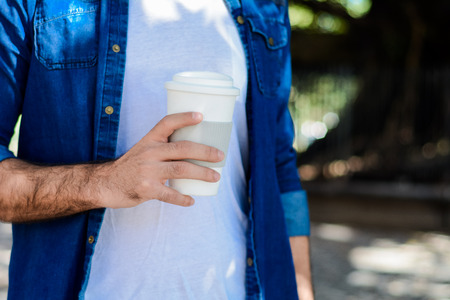 Young handsome man with disposable coffee. Take away concept. Outdoors 版權商用圖片