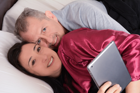 Happy middle-aged couple watching video on tablet at home. Indoors 免版税图像