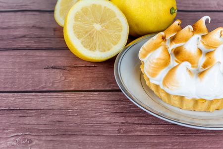 Fresh homemade Lemon pie with meringue and  lemon citrus fruit on wooden table. Stok Fotoğraf