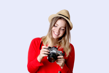 Portrait of young woman in summer hat standing with vintage camera. Travel concept.