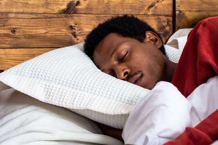 Close-up afro american man sleeping in bed Imagens
