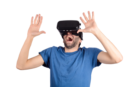 Studio portrait of young guy with VR headset is looking at interactive screen. Man experiencing virtual reality. Stock Photo