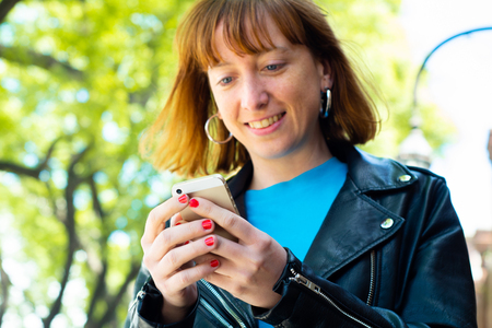 beautiful young redhead woman sending message with smartphone on the street.
