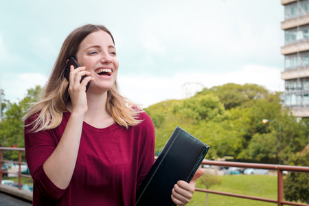 Portrait of young pretty woman talking on her mobile phone. Outdoors. Imagens