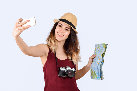Portrait of young tourist woman taking a selfie and holding a map on studio. Stock Photo