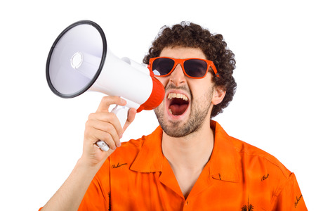 Portrait of young tourist man screaming on a megaphone. Marketing or sales concept.
