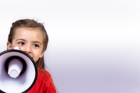 Little girl shouting loud holding a megaphone. Communication and sales concept. Imagens