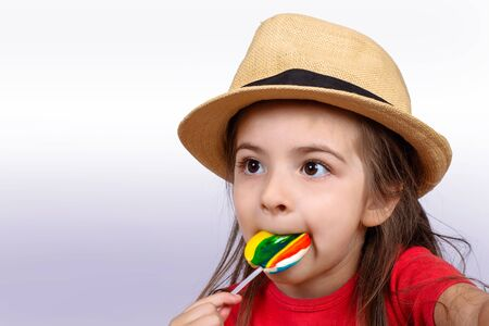 Portrait of little girl eating a colorful lollipop on studio. Stock Photo