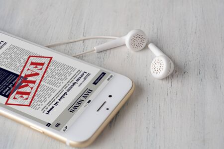 Close up view of earphones and fake News on smartphone. Propaganda and disinformation online. Media and digital concept. All screen graphics are made up by us