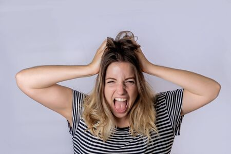 Portrait of beautiful young woman shouting and screaming, studio shoot.