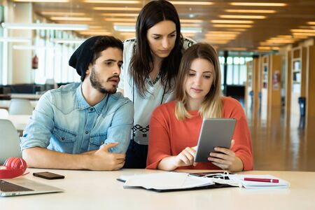 University students sitting together at table using digital tablet. Group study in university library. Education concept Stock Photo