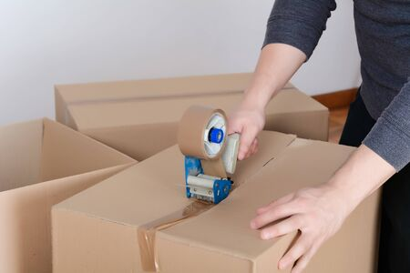 Man sealing a shipping cardboard box with tape dispenser. Indoors Standard-Bild