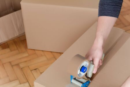 Man sealing a shipping cardboard box with tape dispenser. Indoors Standard-Bild - 131974913