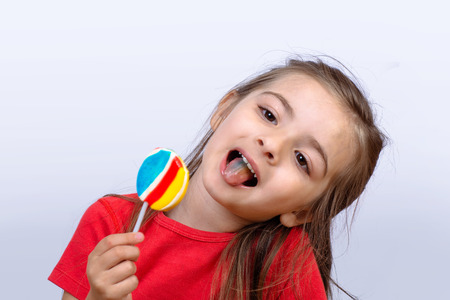 Portrait of little girl eating a colorful lollipop on studio.
