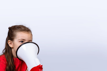 Little girl shouting loud holding a megaphone. Communication and sales concept. Stock Photo