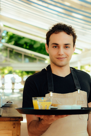 Handsome young waiter holding tray at the coffee shop. Service concept