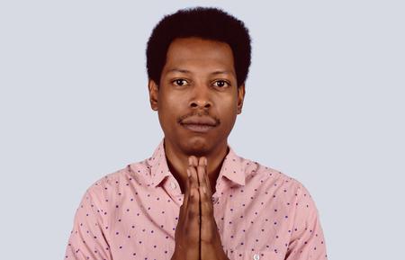 Portrait of Afro American man praying on studio.