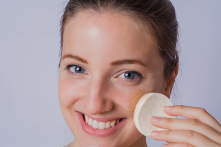 Portrait of young woman applying foundation powder with makeup brush on studio.