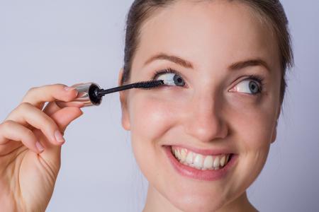 Retrato de joven bella mujer aplicando rímel negro para pestañas en estudio.