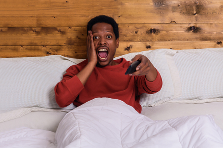 Portrait of young afro american man watching tv and relaxed on bed at home. 免版税图像