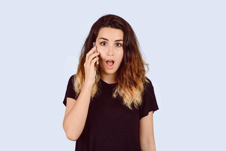 Retrato de mujer joven hermosa hablando por teléfono con mirada sorprendida