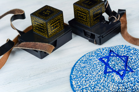 Pair of tefilim with black straps with blue kippah on white wooden background. Jewish lifestyle concept