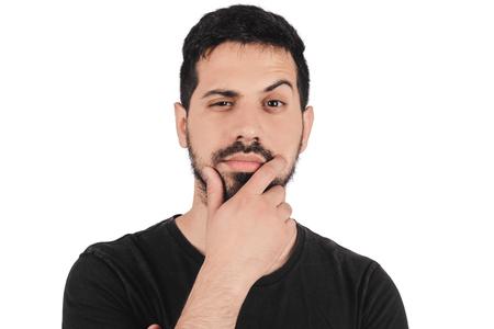 Portret młodego człowieka myślącego ręką w pobliżu twarzy na studio.