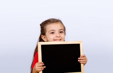Cute little girl kid with blackboard. School concept.