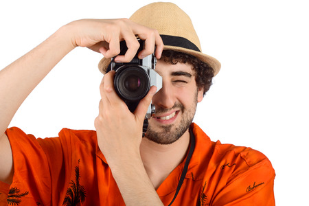 Portrait of a traveler man taking photos with camera on studio. Travel concept.