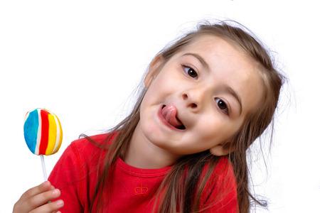 Portrait de petite fille mangeant une sucette colorée en studio.