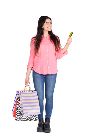 Young beautiful woman with shopping bags and credit card. Shopping, sale concept. Isolated white background.