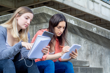 Two University students studying together at the building of university. Education concept