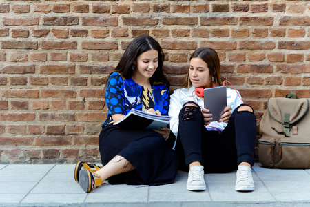 Portrait of two young beautiful women friends using digital tablet. Education concept. Outdoors.