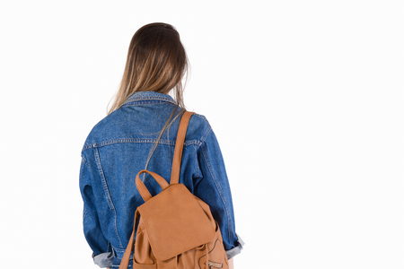 Young woman with backpack on her back on studio.