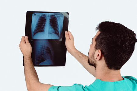 Portrait of male doctor examining xray film. Medical and healthcare concept.