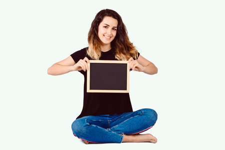 Portrait of young latin woman holding a chalkboard on studio.