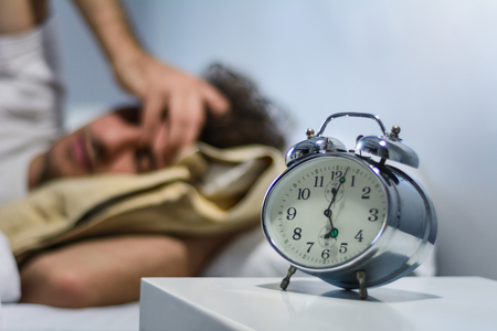 Young latin man hates waking up early in the morning with alarm clock. Indoors. Stock fotó