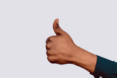Close-up of a hand showing thumbs up on studio.
