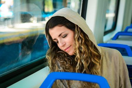 Young urban woman sleeping in a train travel beside the window. Modern people city lifestyle. Standard-Bild