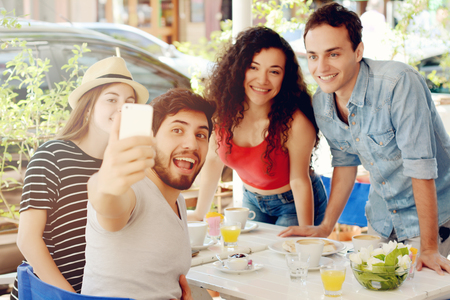 Group of friends taking selfie on a mobile phone in a coffee shop. People having fun together, friendship concept.