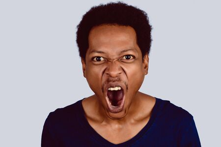 Portrait of Afro American man screaming at camera on studio.