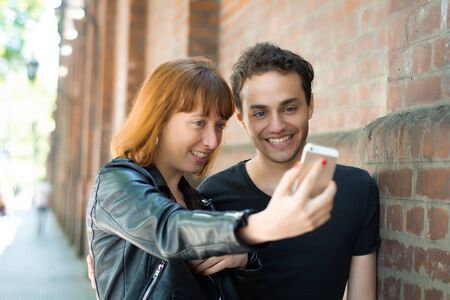 Happy young couple taking selfie with mobile phone in the city. Fun concept.