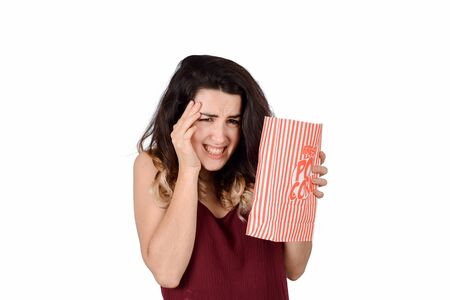 Portrait of Young beautiful woman watching a scary movie and eating popcorn. Isolated white background