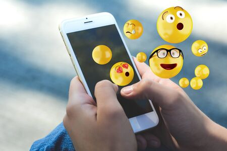 Close-up of woman using smartphone sending emojis. Social concept. 免版税图像