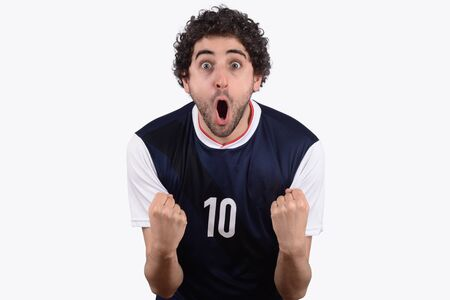 Studio Shot of Young man in soccer football uniform screaming while his team win. Fan, support concept.