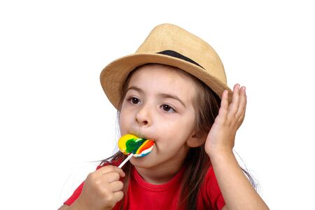 Portrait of little girl eating a colorful lollipop on studio.