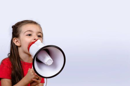 Little girl shouting loud holding a megaphone. Communication and sales concept. Banco de Imagens