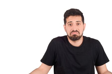 Portrait of a young man who do not understand what is happening. Isolated white background.